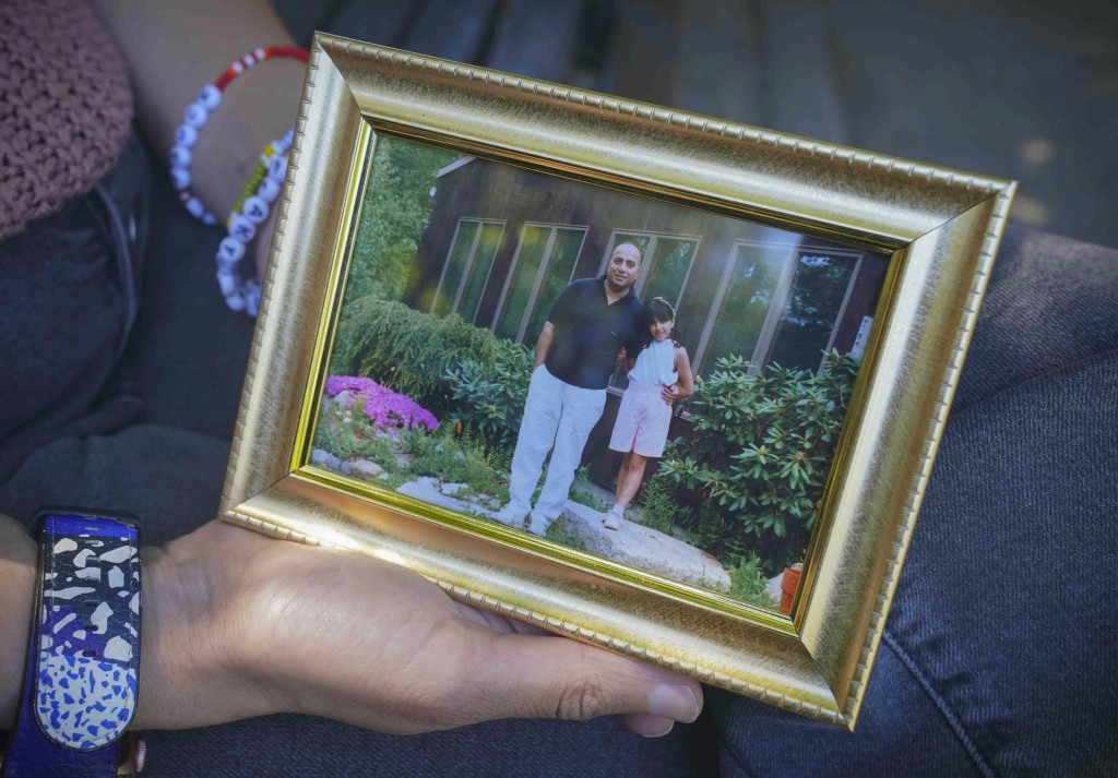 Noreen Wasti shows a framed family photo of herself as a child with her father, Thursday June 24, 2021, in Brooklyn, N.Y. Wasti lost her father Salman...