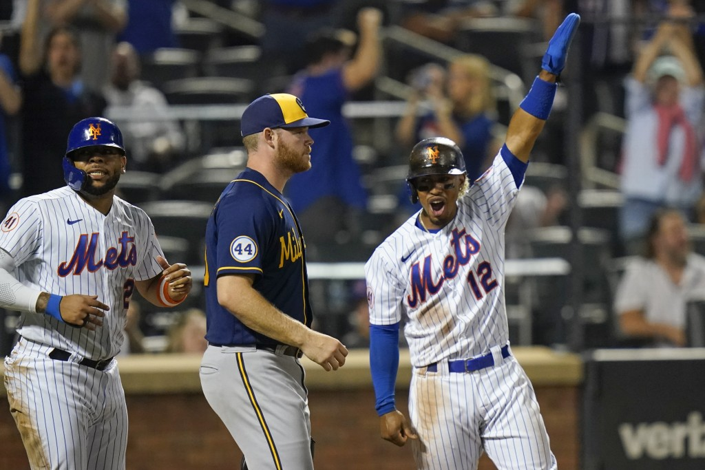 Milwaukee Brewers starting pitcher Brandon Woodruff, center, reacts as New York Mets' Francisco Lindor and Dominic Smith, left, celebrate after scorin...