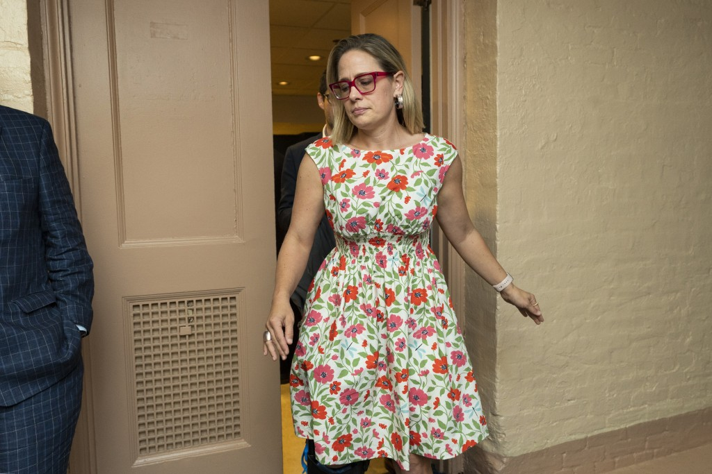 FILE - In this June 22, 2021, file photo, Sen. Kyrsten Sinema, D-Ariz., leaves a closed-door bipartisan infrastructure meeting with a group of senator...