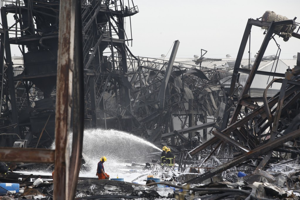 Firefighters spray foam amid twisted metal frames of a charred chemical factory Tuesday, July 6, 2021 in Samut Prakan, Thailand.Firefighters finally e...