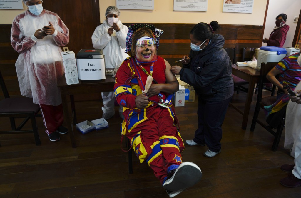 A clown gets a shot of the Sinopharm COVID-19 vaccine during a vaccination campaign targeting people between ages 18 and 30 at the public University S...