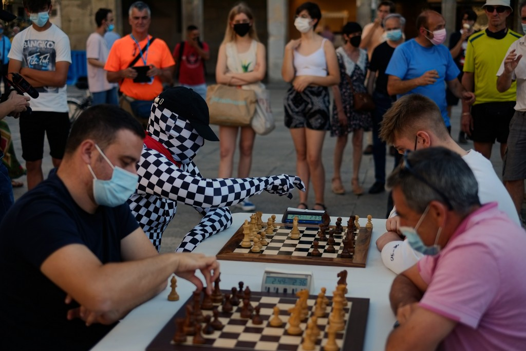 A group of people wearing face protection, one of them with his face and body masked, play chess at Plaza del Castillo square, in Pamplona, northern S...