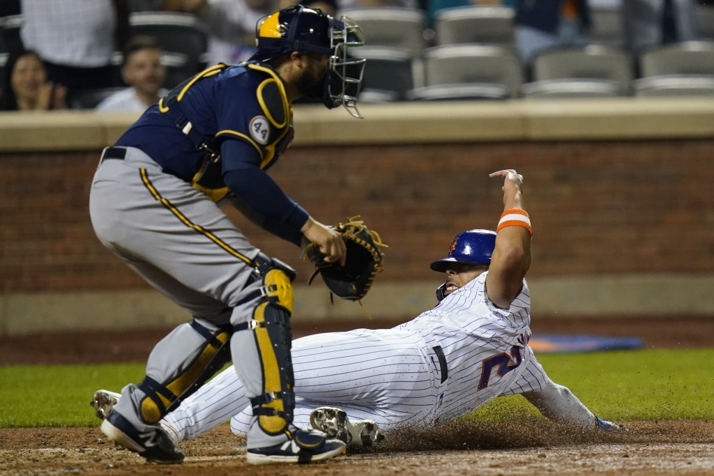 New York Mets' Dominic Smith (2) slides past Milwaukee Brewers catcher Omar Narvaez to score on a double by Pete Alonso during the seventh inning of a...