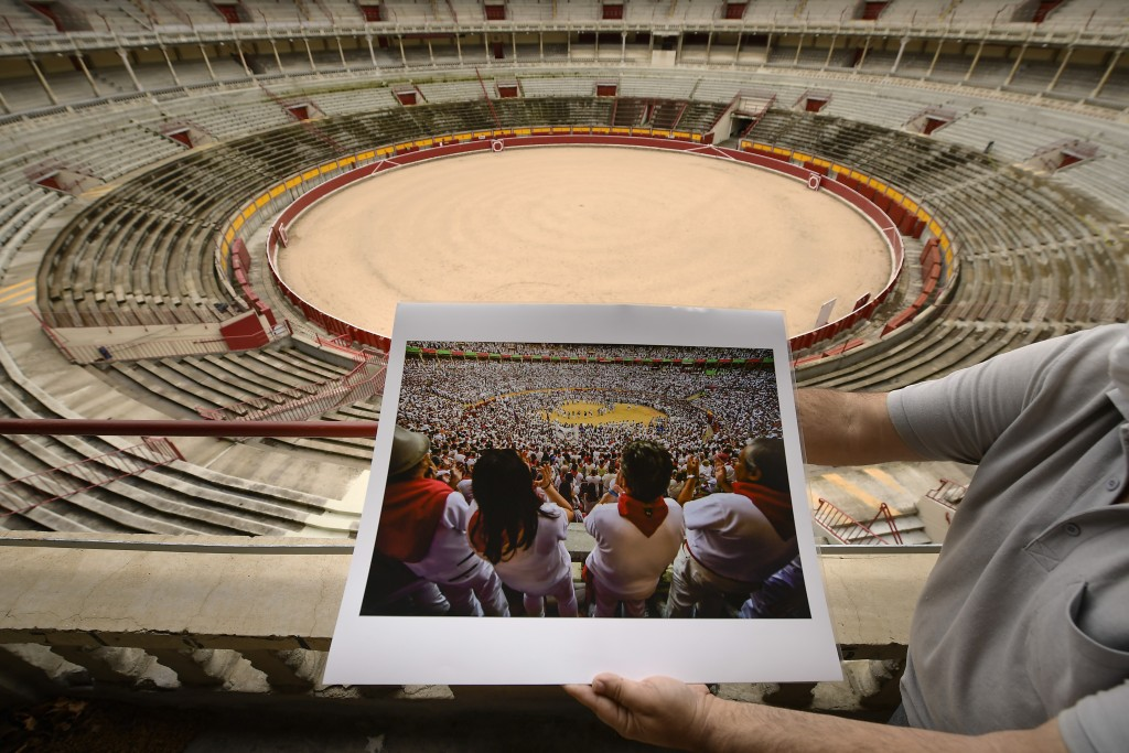 A person holds a July 2019 San Fermin photograph in front of the empty bull ring in Pamplona, northern Spain, Tuesday July 6, 2021, during the famous ...