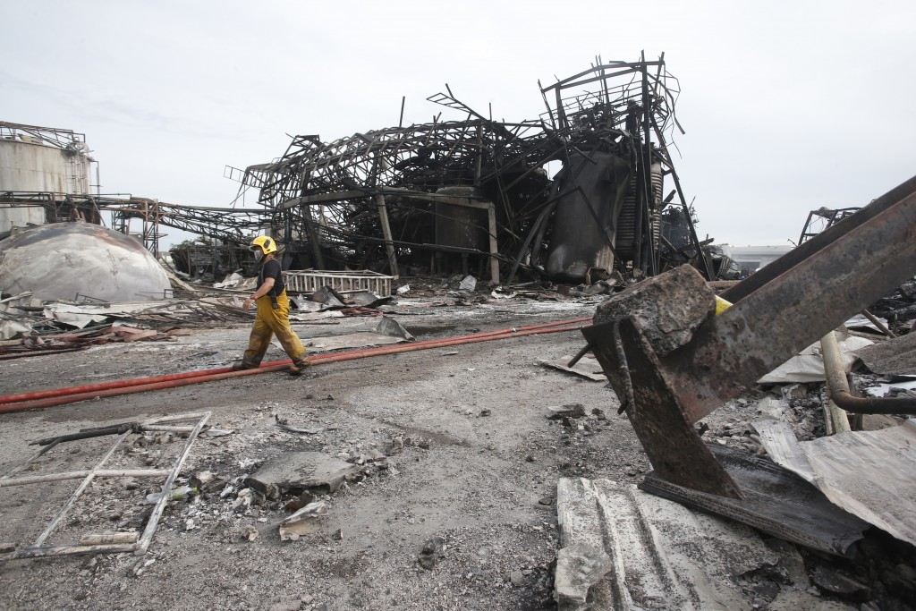 A firefighter walks in front of twisted metal frames of a charred chemical factory Tuesday, July 6, 2021, in Samut Prakan, Thailand. Firefighters fina...
