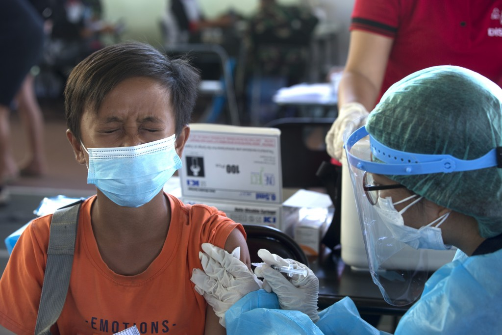 A teenager reacts as he receives a shot of the Sinovac vaccine for COVID-19 during a vaccination campaign in Bali, Indonesia, Tuesday, July 6, 2021. (...