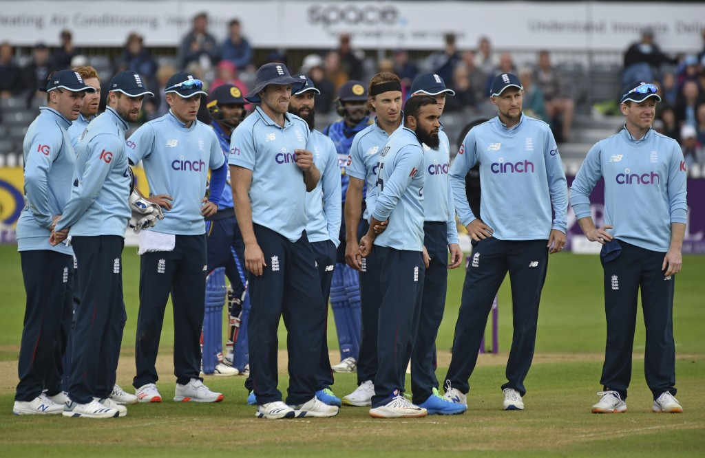 FILE - In this Sunday, July 4, 2021 file photo England's captain Eoin Morgan, right, and teammates await third umpire's decision for the wicket of Sri...