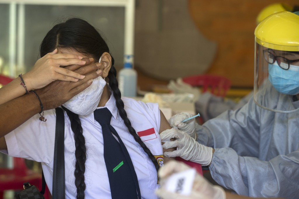A teenager reacts as she receives a shot of the Sinovac vaccine for COVID-19 during a vaccination campaign at a school in Denpasar, Bali, Indonesia on...