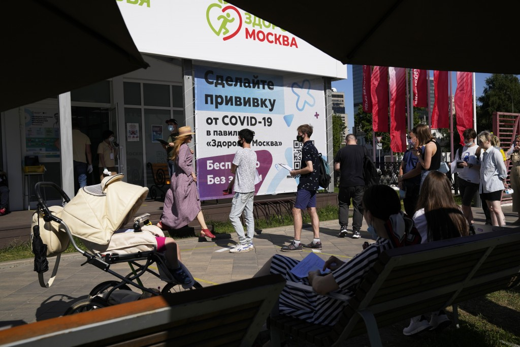 People wait in line for a COVID-19 vaccine at a vaccination center in a park in Moscow, Russia, Tuesday, July 6, 2021. Russia on Sunday reported about...