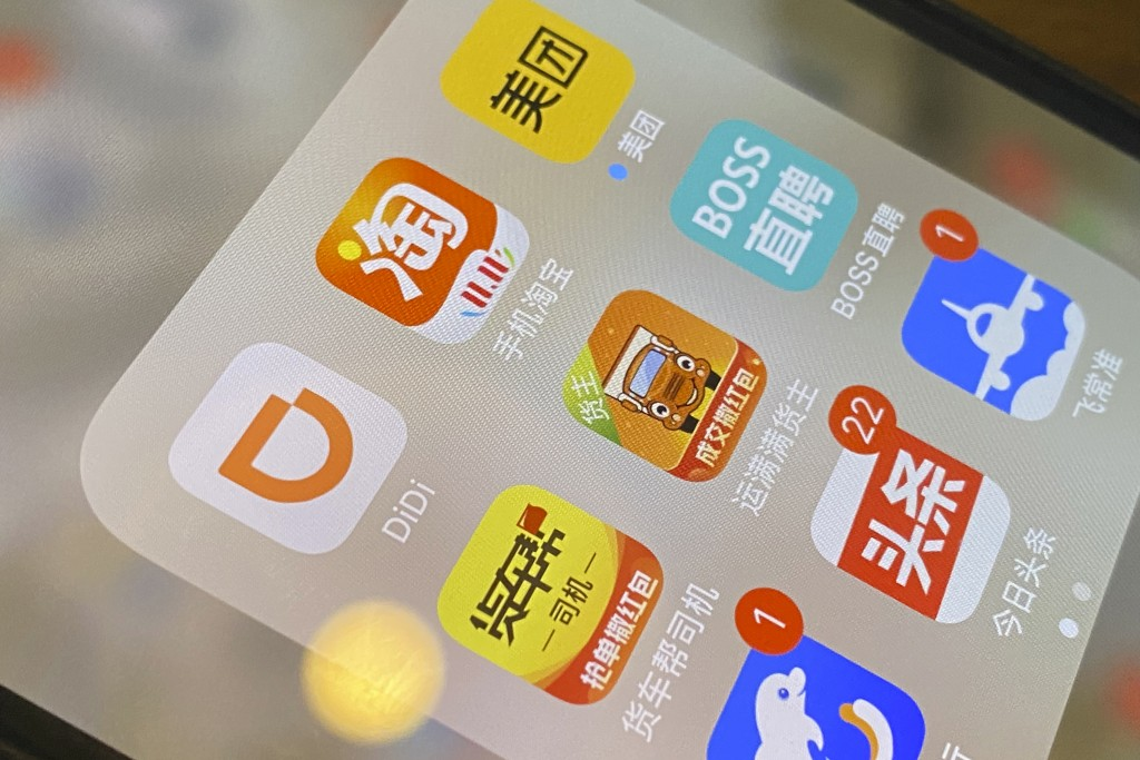 The ride-hailing app Didi is seen near other Chinese apps on a phone in Beijing on Monday, July 5, 2021. Chinese regulators have clamped down on the c...
