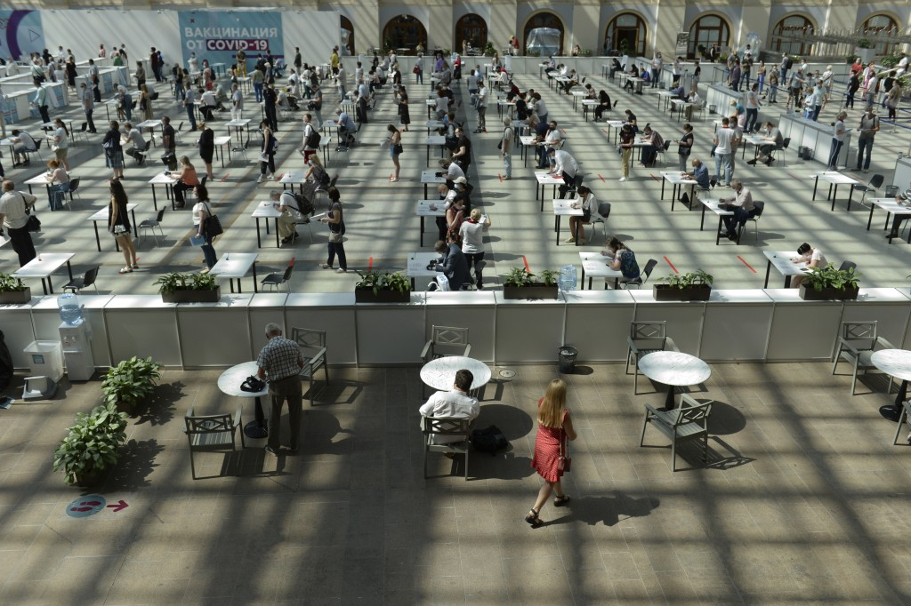 People wait in line for a COVID-19 vaccine at a vaccination center in Gostinny Dvor, a huge exhibition place in Moscow, Russia, Tuesday, July 6, 2021....