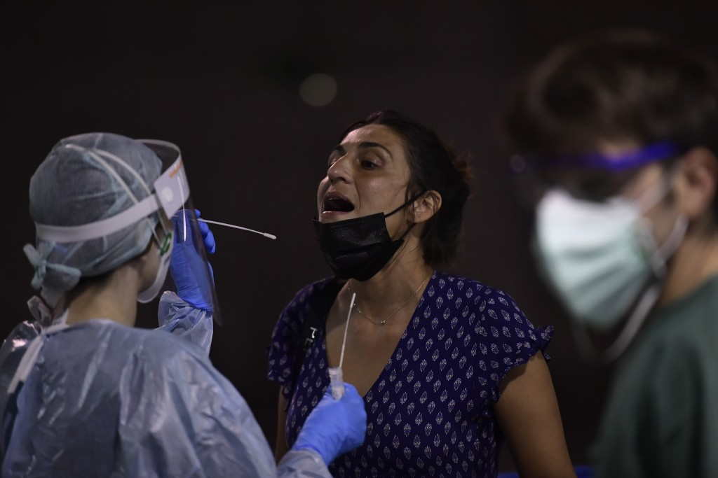 A health worker takes a swab from a teenager during a rapid antigen test for COVID-19 in Pamplona, northern Spain, Monday, July 5, 2021. During the la...