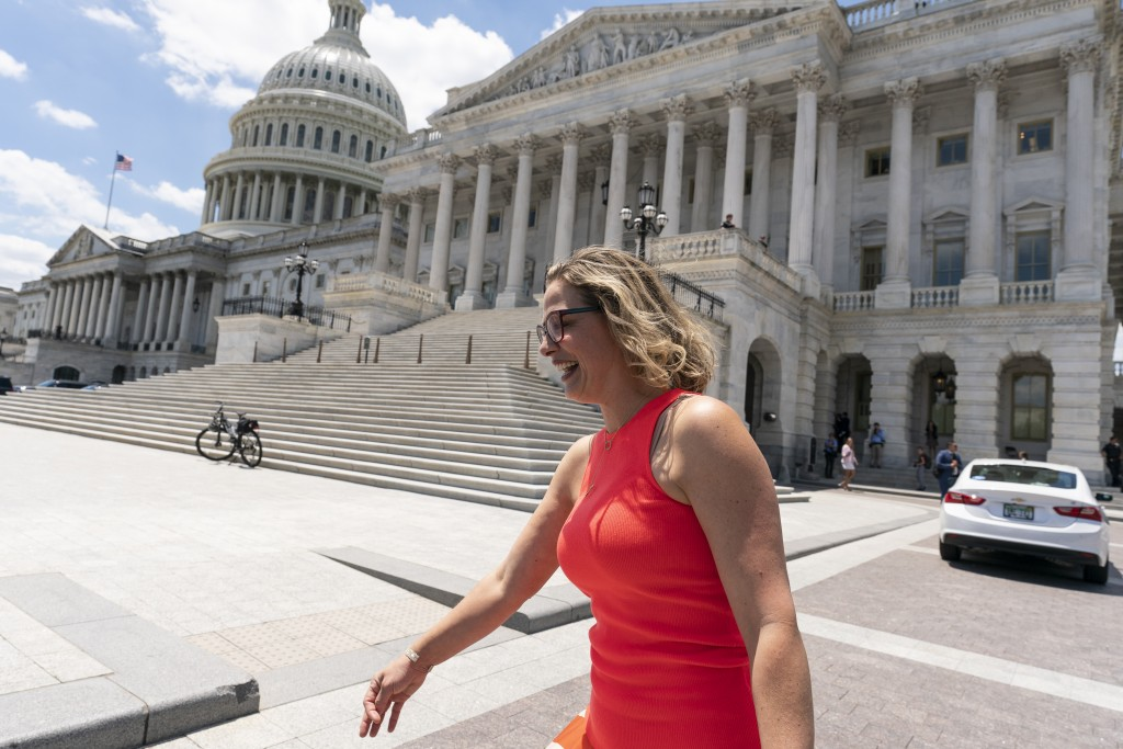 FILE - In this June 24, 2021, file photo, Sen. Kyrsten Sinema, D-Ariz., smiles as she returns to the Capitol after a meeting with President Joe Biden ...