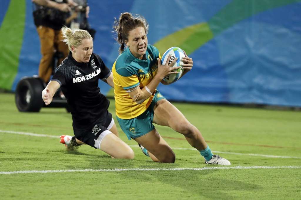 FILE - In this Aug. 8, 2016, file photo, Australia's Evania Pelite, right, scores a try as New Zealand's Kelly Brazier chases during the women's rugby...