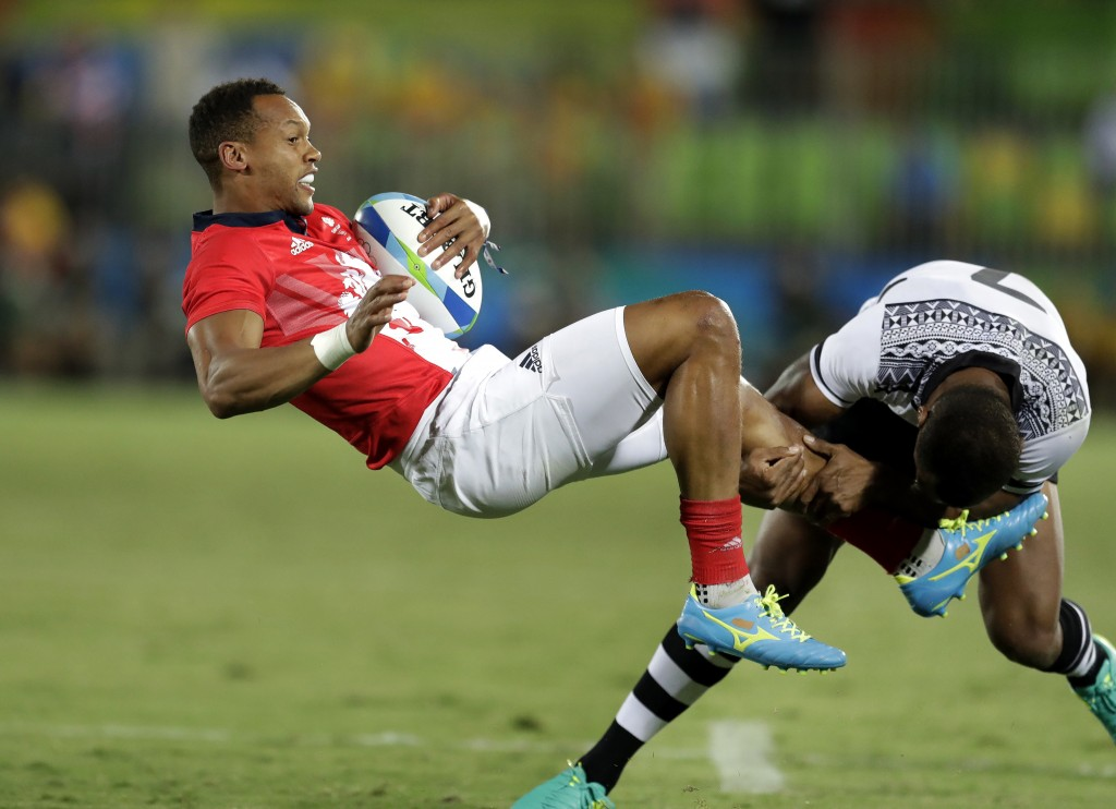 FILE - In this Aug. 11, 2016, file photo, Britain's Dan Norton, left, is tackled by Fiji's Osea Kolinisau, during the men's rugby sevens gold medal ma...