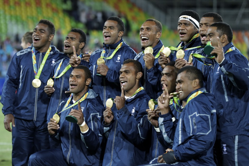 FILE - In this Aug. 11, 2016, file photo, Fiji rugby players show off their gold medal after defeating Britain in the gold medal mens rugby sevens mat...