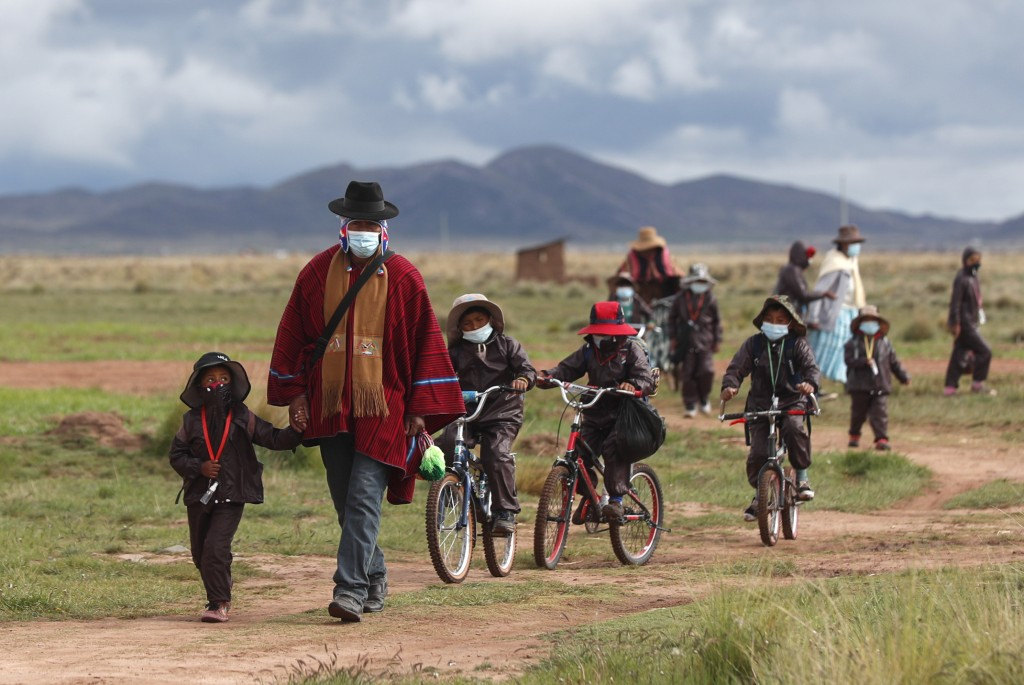 FLE - In this Feb. 4, 2021 file photo, Aymara Indigenous parents walk their children wearing new, protective uniforms to Jancohaqui Tana school as the...