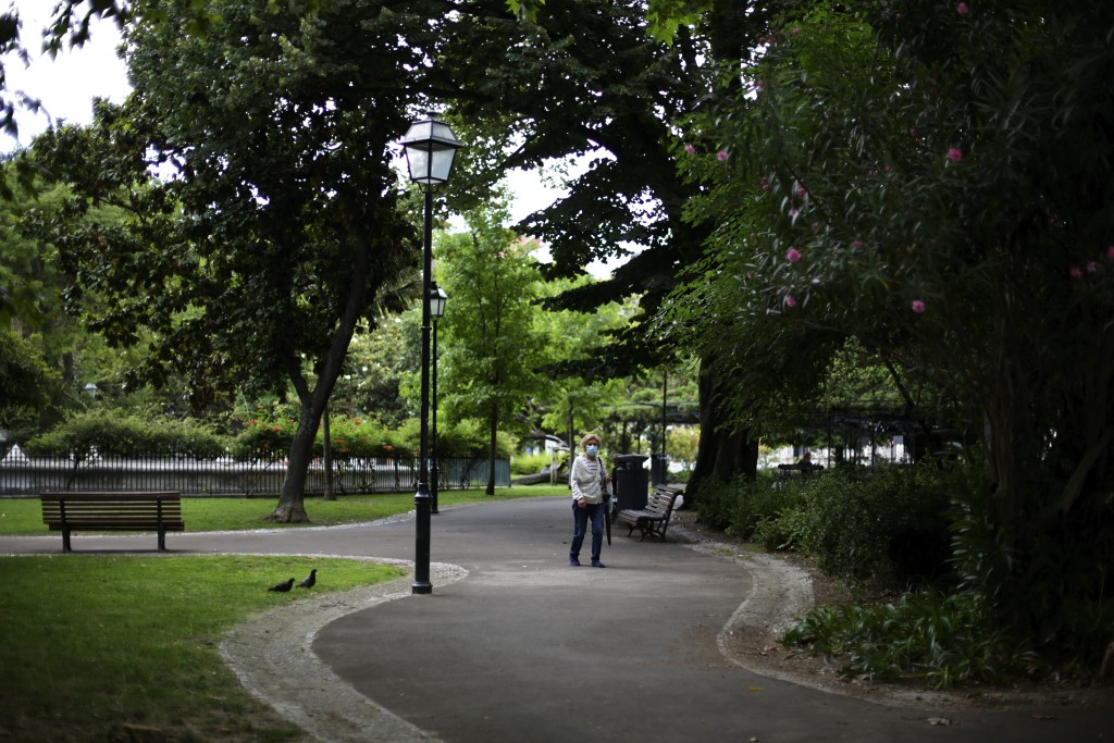 A woman wearing a face mask walks in a public garden in Lisbon, Tuesday, July 6, 2021. Admissions of COVID-19 patients in hospitals are at a two-month...
