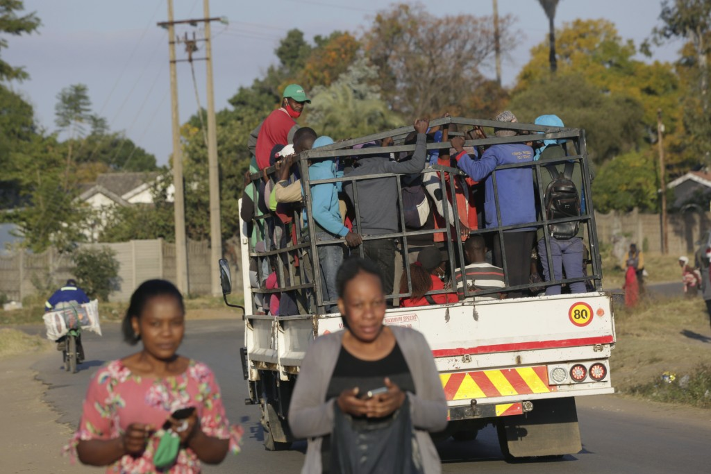 A truck loaded with people travels on a street, in Harare, Tuesday, July, 6, 2021. Zimbabwe has reactivated strict lockdown measures it once imposed w...