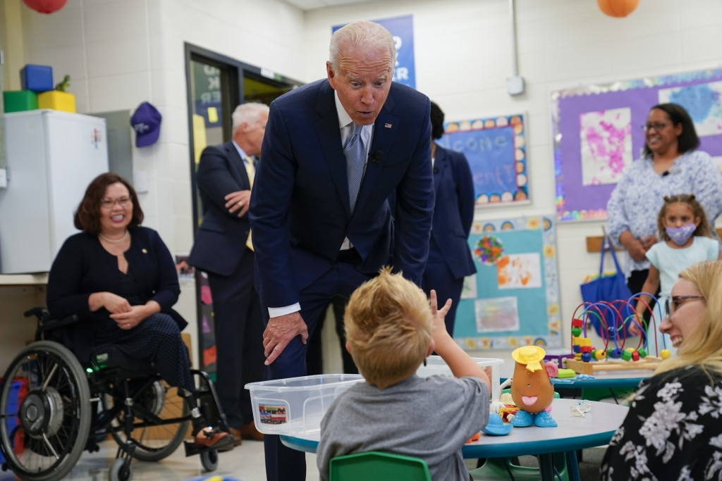President Joe Biden speaks to a child as he tours a children's learning center at McHenry County College, Wednesday, July 7, 2021, in Crystal Lake, Il...