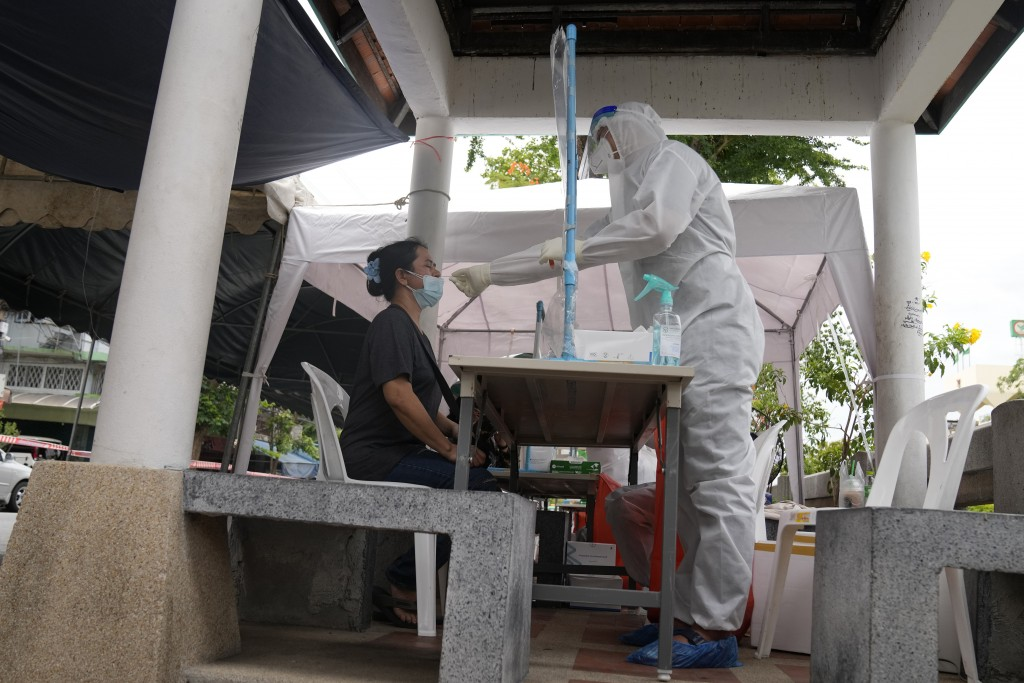 A Health worker collect nasal swabs from local residents for coronavirus testing in Bangkok, Thailand, Thursday, July 8, 2021. (AP Photo/Sakchai Lalit...
