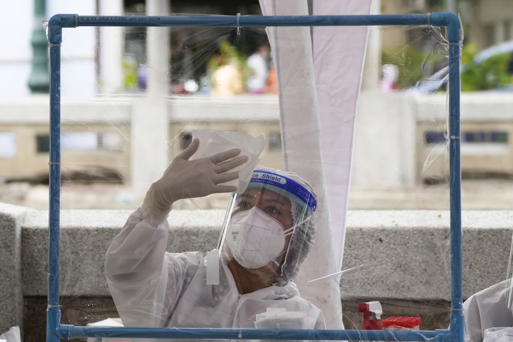 A Health worker disinfects plastic sheets after collecting nasal swabs from local residents for coronavirus testing in Bangkok, Thailand, Thursday, Ju...