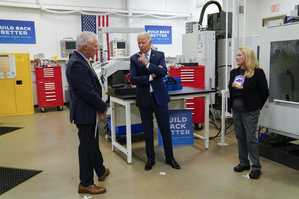 President of McHenry County College Clint Gabbard, listens as President Joe Biden speaks as he tours a manufacturing lab at McHenry County College dur...