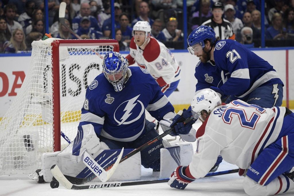 Montreal Canadiens center Eric Staal (21) and Tampa Bay Lightning center Brayden Point (21) reach for the puck next to Lightning goaltender Andrei Vas...