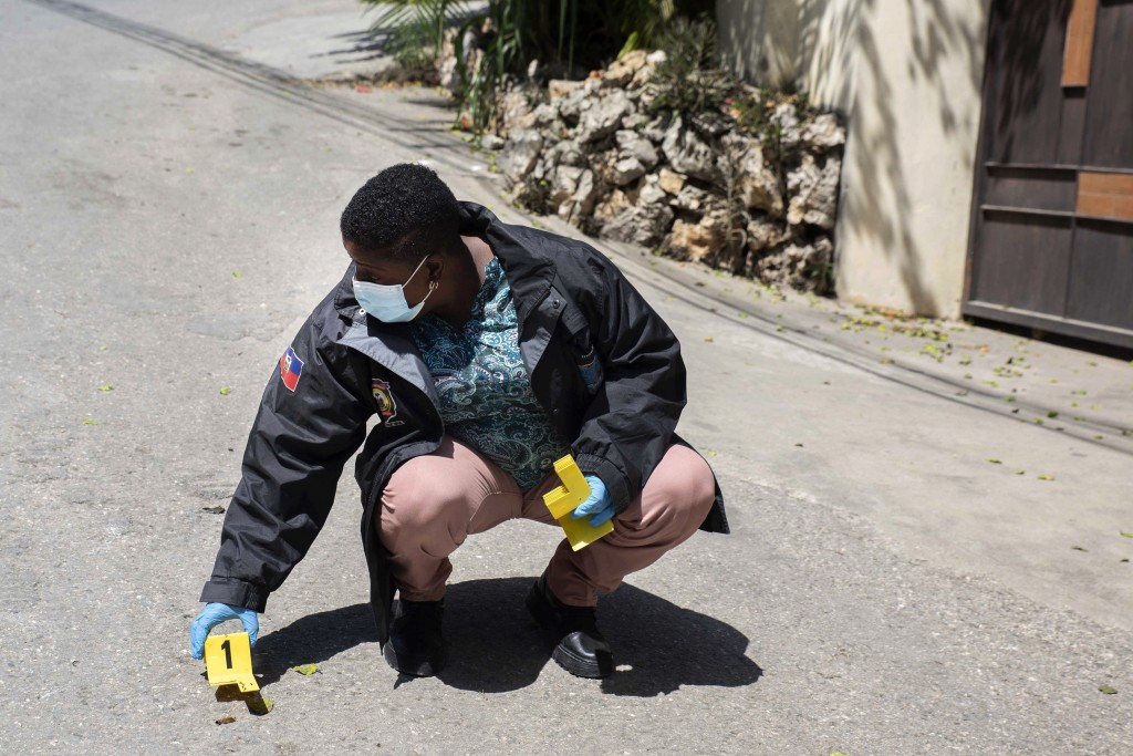 An investigator places an evidence marker next to a bullet casing outside the residence of Haitian President Jovenel Moise, in Port-au-Prince, Haiti, ...