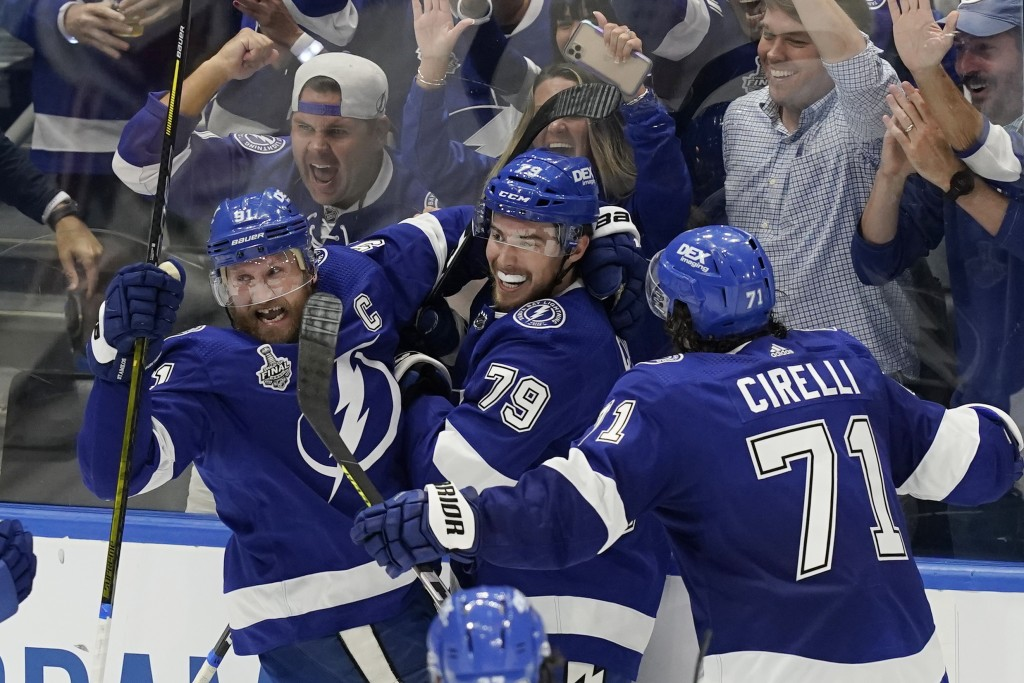 Tampa Bay Lightning center Steven Stamkos, left, and center Anthony Cirelli (71) crowd left wing Ross Colton (79) after scoring on Montreal Canadiens ...