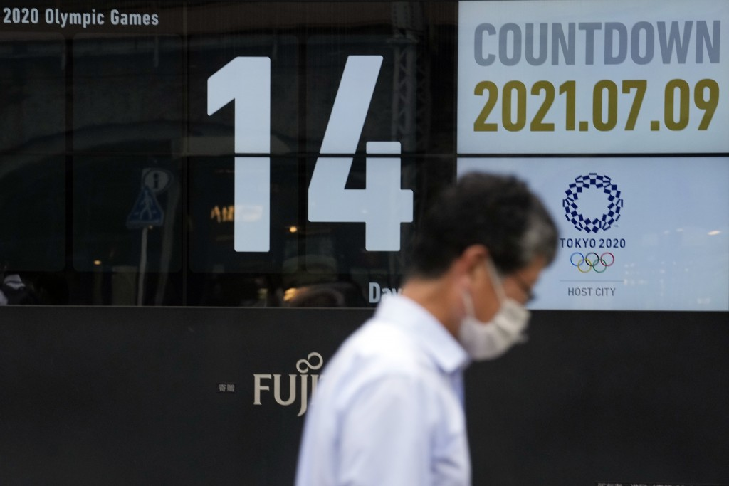 A man wearing a face mask walks past the countdown clock for the Tokyo 2020 Olympic Games near the Shimbashi train station Friday, July 9, 2021, in To...