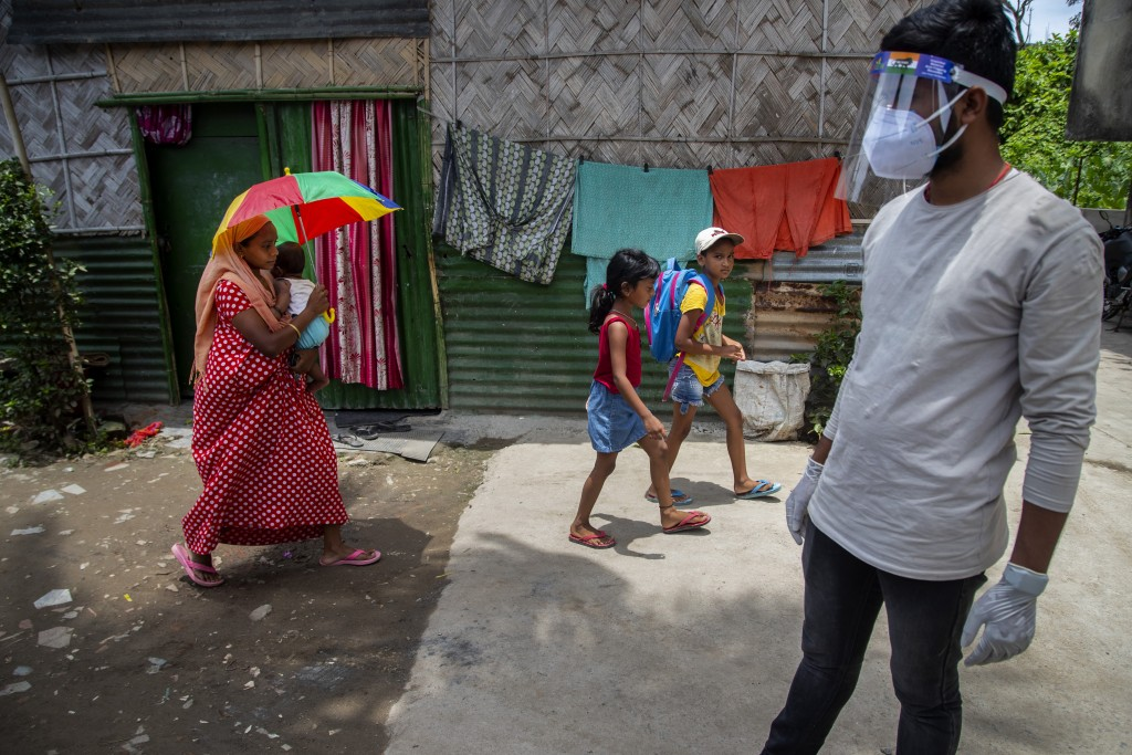 A health worker arrives in a residential neighborhood to collect swab samples from residents to test for COVID-19 during a door-to-door testing drive ...