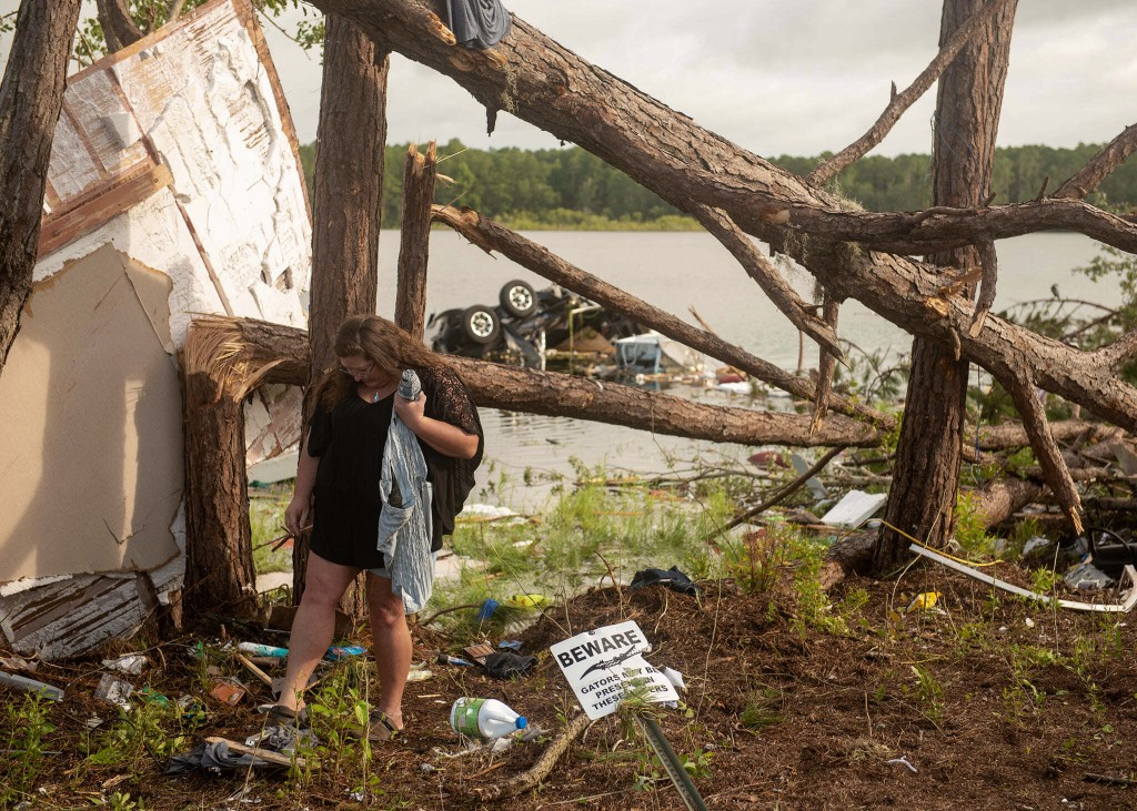This photo provided by the U.S. Navy, Missy Lattanzie, an RV park resident, searches through her belongings that were destroyed after a tornado touche...