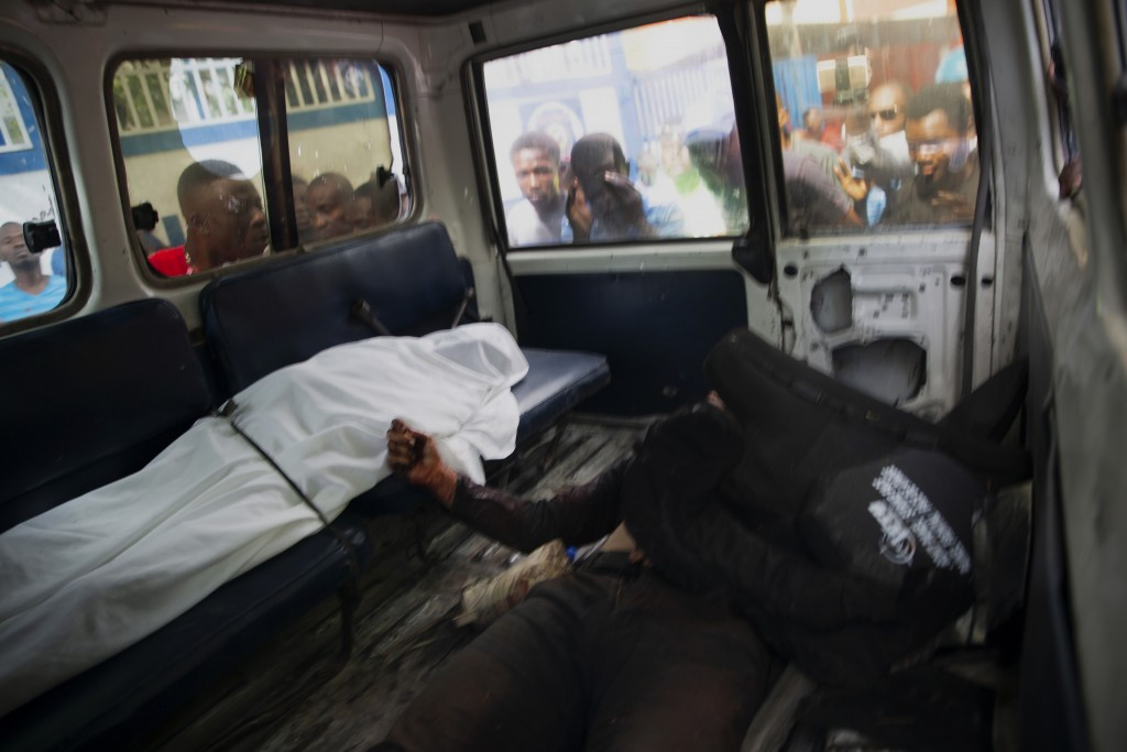 People look into the window of a police car carrying the bodies of two people killed in a shooting with police in Port-au-Prince, Haiti, Thursday, Jul...