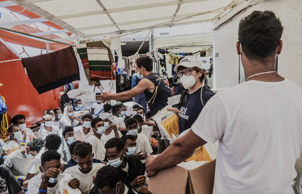 Staffers distribute food to migrants on the deck of the Ocean Viking rescue in the Mediterranean Sea on Monday, July 5, 2021. A charity rescue ship wi...