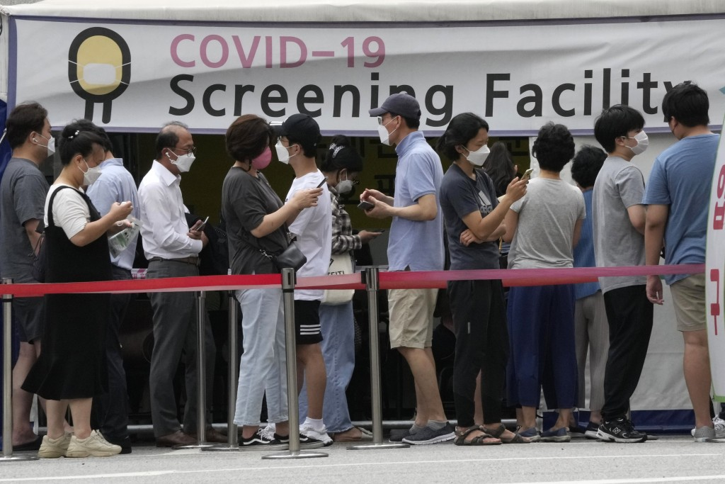 People queue in line to wait for the coronavirus testing at a Public Health Center in Seoul, South Korea, Friday, July 9, 2021. South Korea will enfor...