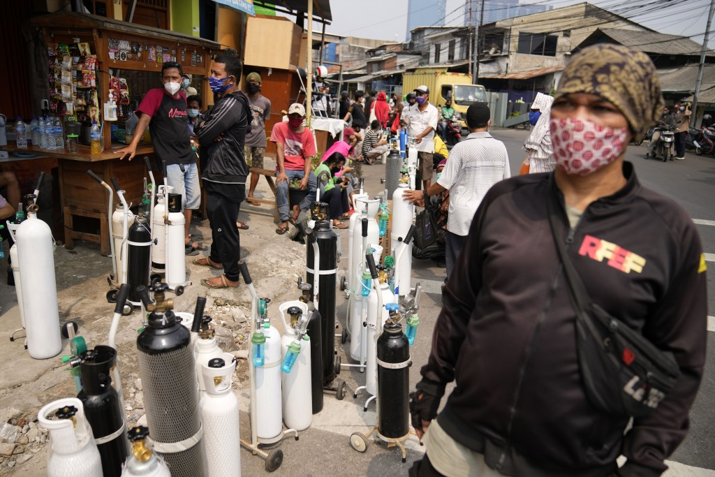 In this July 5, 2021, file photo, people queue up to refill their oxygen tanks at a filling station in Jakarta, Indonesia. Faced with rapidly rising n...