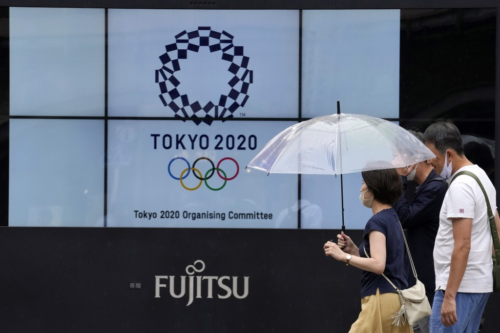 People wearing face masks walk past the logo of the Tokyo 2020 Olympic Games near the Shimbashi train station, Friday, July 9, 2021, in Tokyo. The cou...