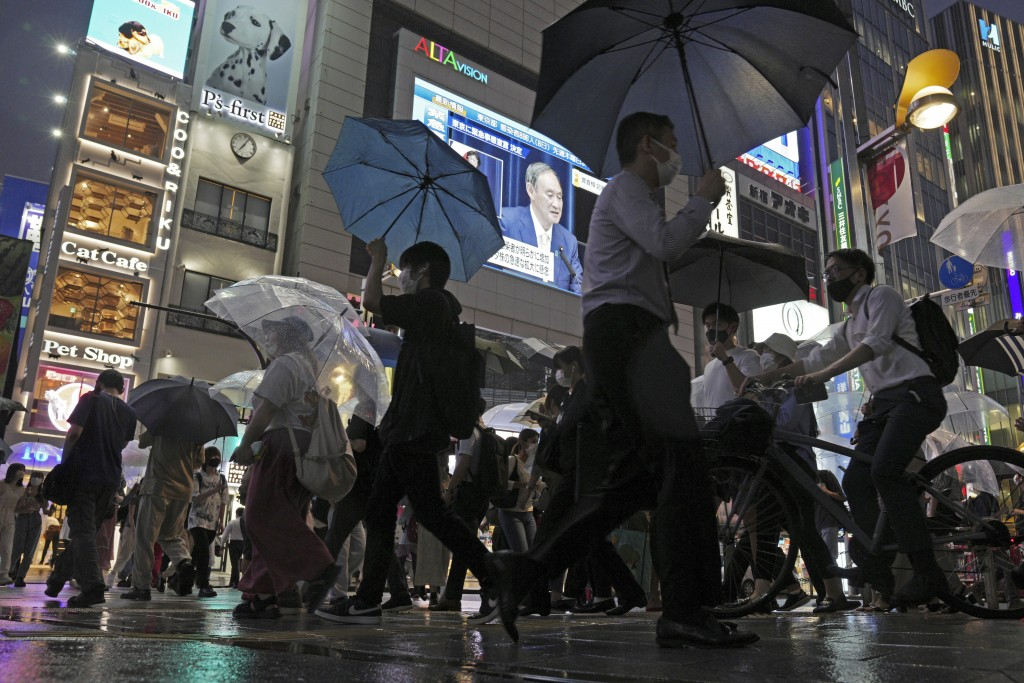 In this July 8, 2021, file photo, pedestrians walk past a giant public TV with a live broadcast of a news conference by Japanese Prime Minister Yoshih...