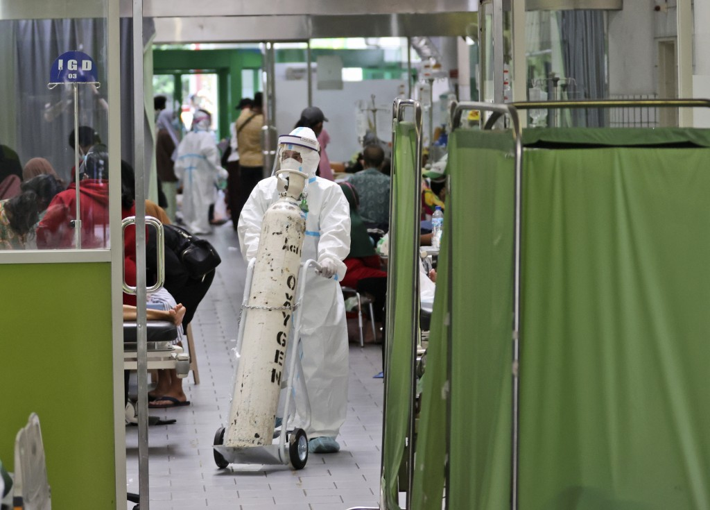 A paramedic pushes an oxygen tank at the emergency ward of an overcrowded hospital amid COVID-19 cases, in Surabaya, East Java, Indonesia, Friday, Jul...