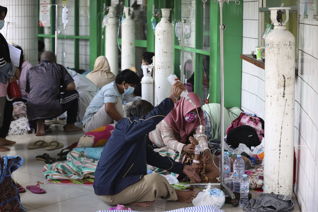 Oxygen tanks are prepared for patients in the hallway of an overcrowded hospital amid a surge of COVID-19 cases, in Surabaya, East Java, Indonesia, Fr...