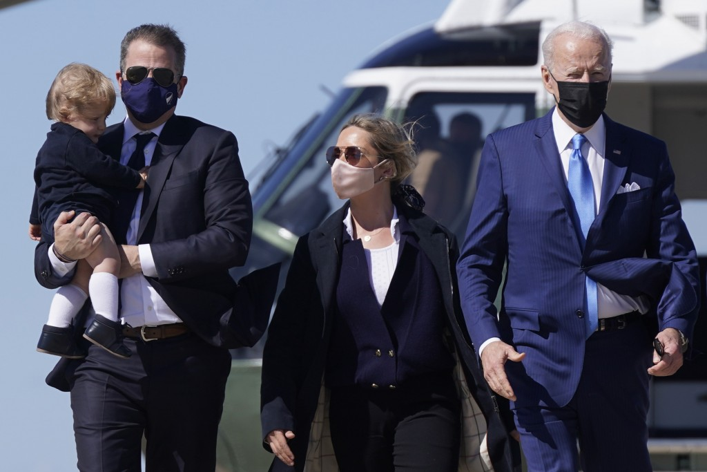 FILE - In this March 26, 2021, file photo President Joe Biden walks with his son Hunter Biden, second from left, as Hunter carries his son Beau and wa...