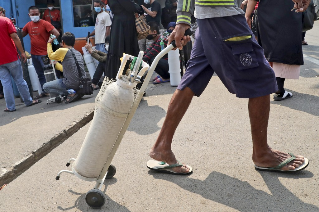 A man leaves with his full oxygen canister as others wait to refill their tanks at a recharging station in Jakarta, Indonesia, Friday, July 9, 2021. J...