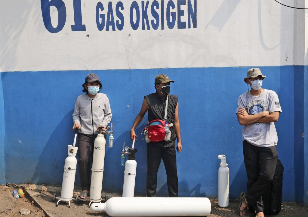 People wait for their turn to refill their oxygen tanks at a recharging station in Jakarta, Indonesia, Friday, July 9, 2021. The world's fourth most p...