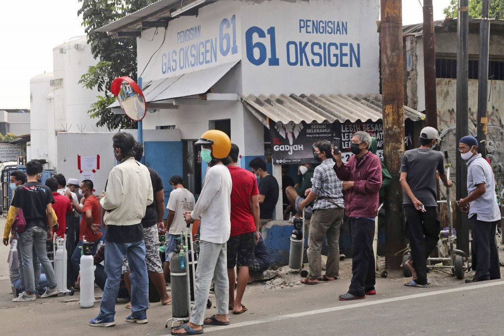People wait for their turn to refill their oxygen tanks at a recharging station in Jakarta, Indonesia, Friday, July 9, 2021. Just two months ago, Indo...