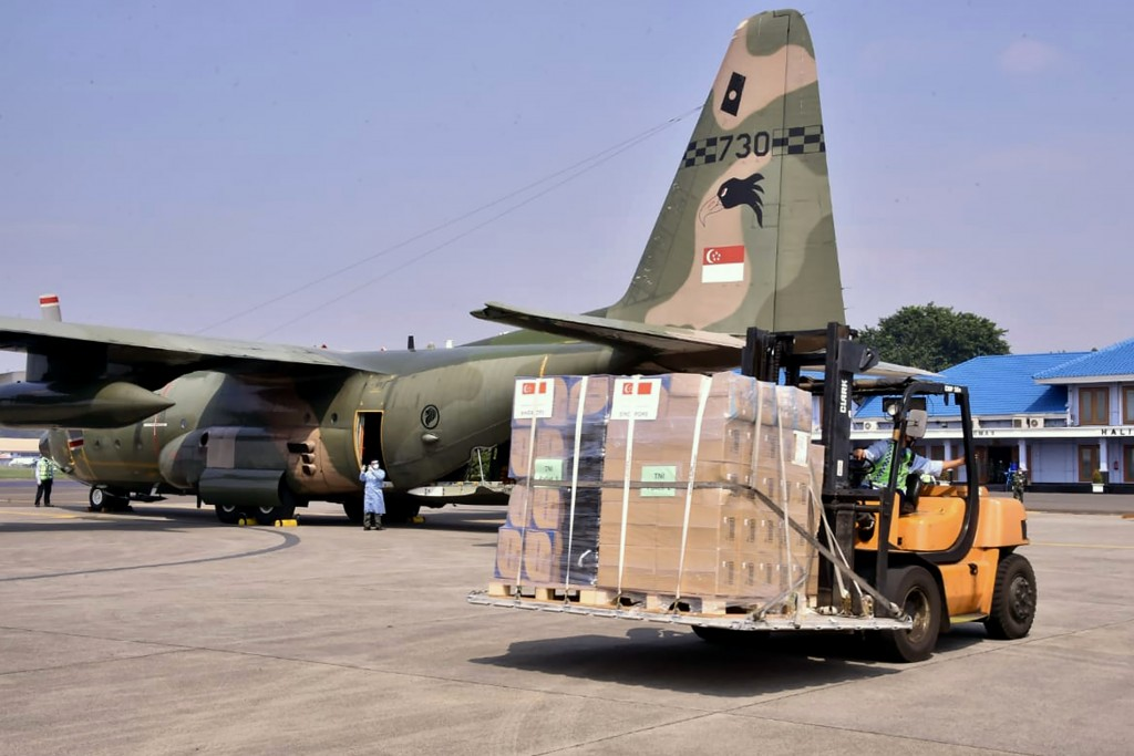 In this photo released by Indonesian Armed Forces, a military personnel uses a forklift to unload relief goods from a Singaporean Air Force cargo plan...