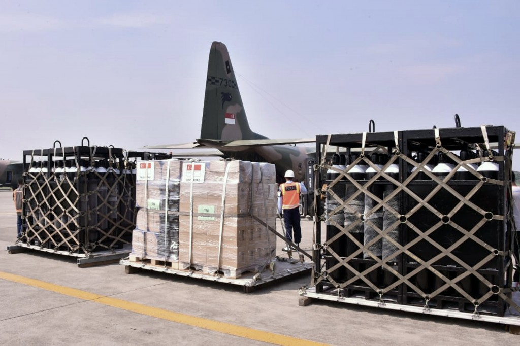 In this photo released by Indonesian Armed Forces, a military personnel stand guard near oxygen canisters and other relief goods unloaded from a Singa...