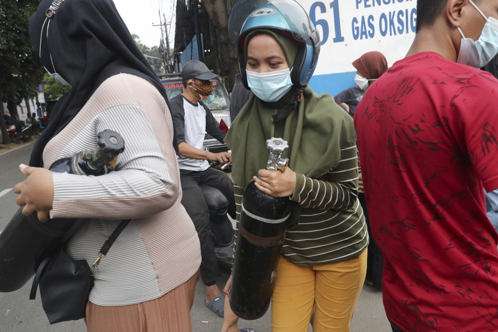 A woman carries her oxygen tank after having it refilled at a recharging station in Jakarta, Indonesia, Friday, July 9, 2021. The world's fourth most ...