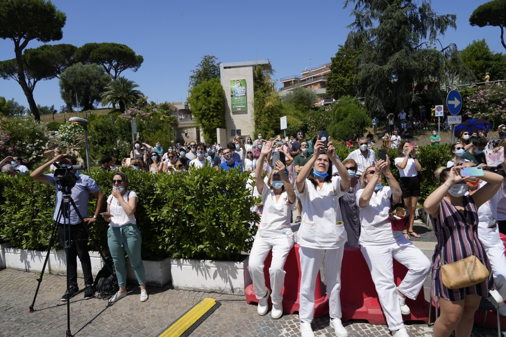 Faithful and paramedics listen to Pope Francis as he appears on a balcony of the Agostino Gemelli Polyclinic in Rome, Sunday, July 11, 2021, where he ...