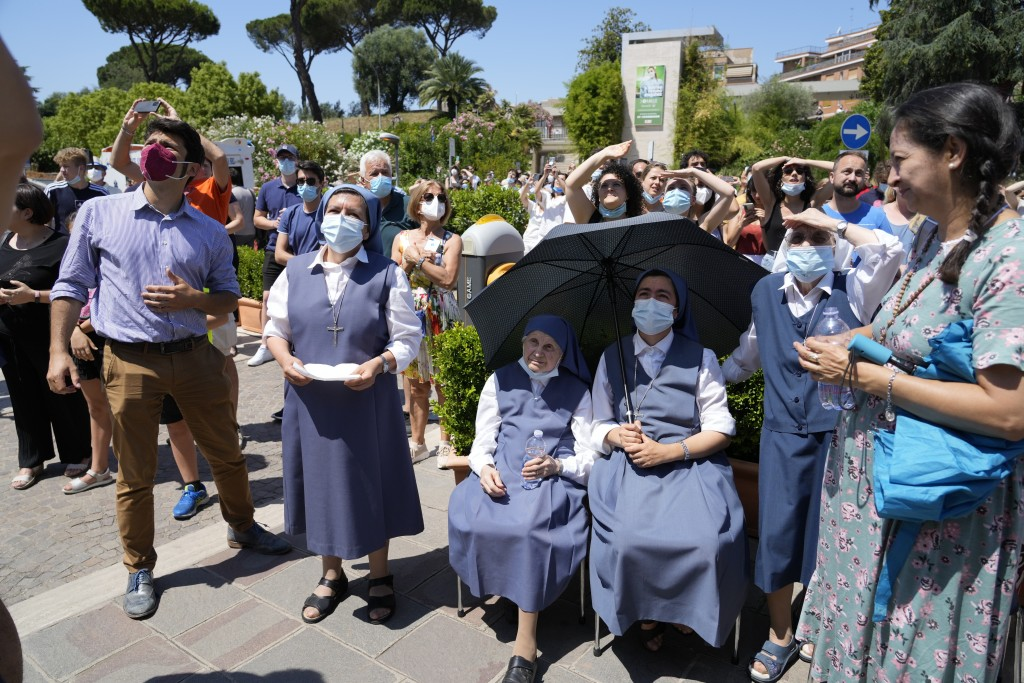 Faithful listen to Pope Francis appearing on a balcony of the Agostino Gemelli Polyclinic in Rome, Sunday, July 11, 2021, where he is recovering from ...
